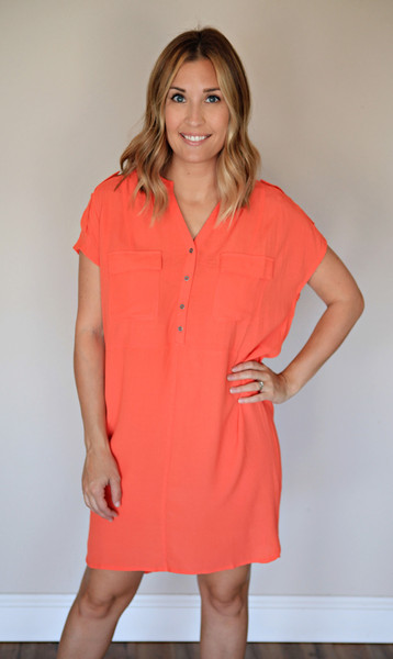 The Scout Dress is a coral colored t-shirt dress with buttons.