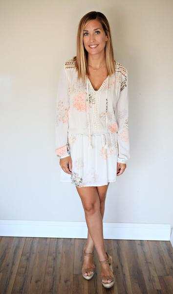 The Caelyn Dress is a white flowery long sleeve dress with tassel ties.
