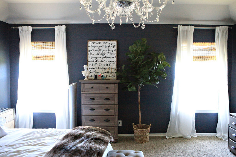 Master bedroom featuring navy walls, white bedding, tufted linen headboard and bench